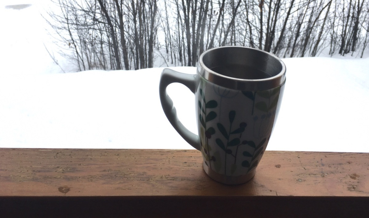 Mug with hot tea on a wooden railing