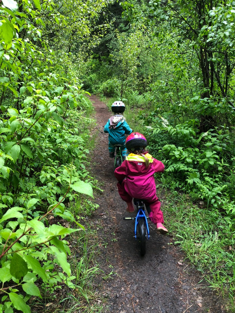 little girls biking on a nature trail
